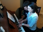 Tess is teaching Trevor how to play the piano duet style.
